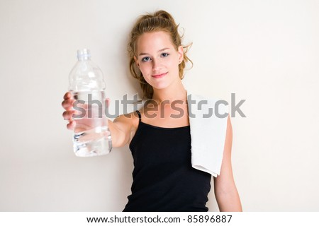 Portrait of beautiful young blond woman offering water. - stock photo