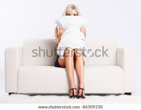portrait of beautiful young blond woman sitting on couch with remote control watching scary movie and hiding behind the pillow - stock photo
