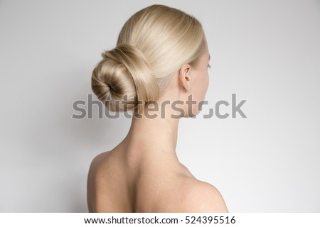 Portrait Of Beautiful Young Blond Woman With Bun Hairsty?le. Back View