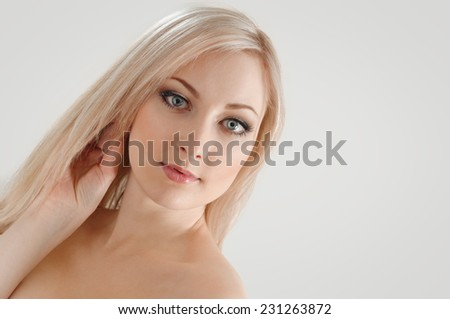Portrait of beautiful young blond woman with clean face. on grey - stock photo