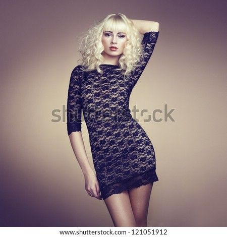 Portrait of beautiful young blonde girl in black dress. Fashion photo - stock photo