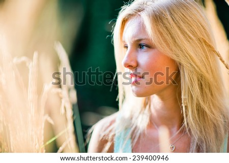 portrait of beautiful young blonde woman in wheat field variation - stock photo