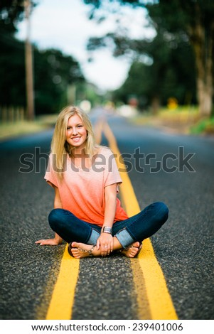 portrait of beautiful young blonde woman sitting in road legs crossed vertical leaning - stock photo