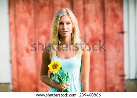 portrait of beautiful young blonde woman standing in front of red wall holding sunflower - stock photo