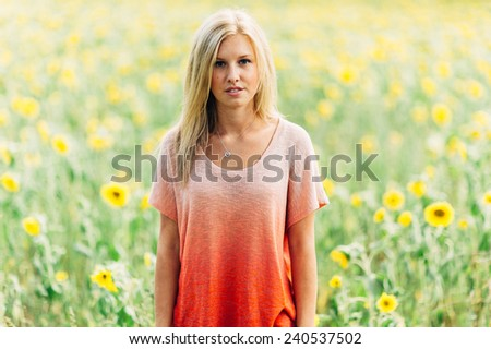 portrait of beautiful young blonde woman standing in front of sunflowers - stock photo