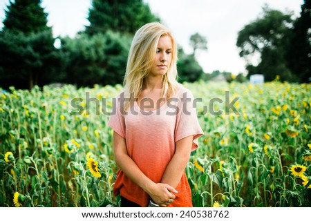 portrait of beautiful young blonde woman standing in front of sunflowers hand on arm looking down - stock photo