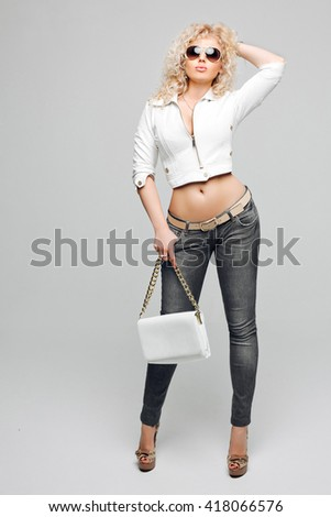 Portrait of beautiful young blonde woman with curly hair. The girl wore a white leather jacket, blue jeans and sunglasses in Studio grey background. Studio portrait. White leather handbag in hand - stock photo