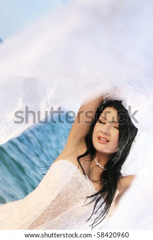 Portrait of beautiful young bride at the sea coast
