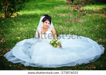 portrait of beautiful young bride holding bright bouquet of flowers in hands. wedding celebration. reception. nature green background. woman alone outdoors in park. - stock photo