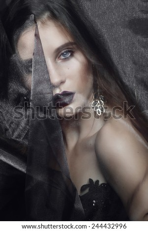 Portrait of beautiful young brunette girl in the studio with a veil in the Gothic style - stock photo