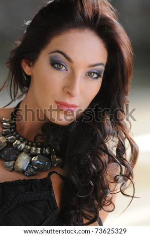 portrait of beautiful young brunette girl with full volume brown hair, evening make-up and gemstone necklace - stock photo