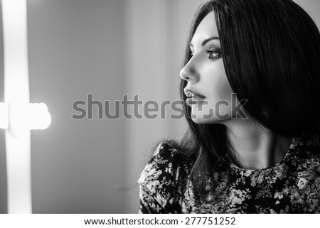 Portrait of beautiful young brunette posing indoors - stock photo