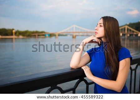 Portrait of beautiful young brunette posing near the river - stock photo