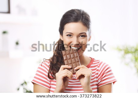Portrait of beautiful young brunette with chocolate in the room , close up - stock photo