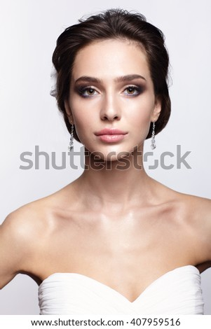 Portrait of beautiful young brunette woman bride in white Wedding Dress on light gray background
