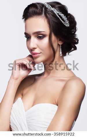 Portrait of beautiful young brunette woman bride with hand near face in white Wedding Dress on light gray background - stock photo