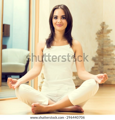 Portrait of beautiful young brunette woman doing yoga exercises, indoors