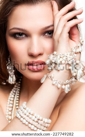 Portrait of beautiful young brunette woman in and earrings  touching her face