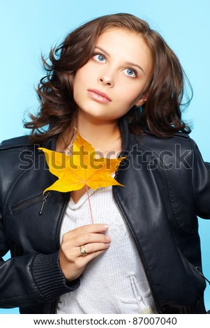 portrait of beautiful young brunette woman in black leather jacket with yellow autumn maple leaf on blue