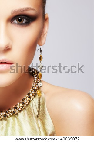portrait of beautiful young brunette woman in ear-rings and collar - stock photo