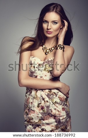 portrait of beautiful young brunette woman in golden jewelry, flower pattern dress - stock photo