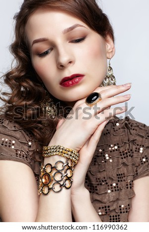 portrait of beautiful young brunette woman in jewelry with both hands under chin