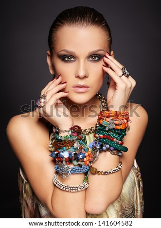 portrait of beautiful young brunette woman in multiple bracelets and rings on dark gray