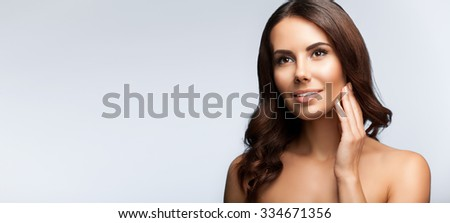 portrait of beautiful young brunette woman, looking up, with naked shoulders, on bright grey background, with blank copyspace area for slogan or text - stock photo