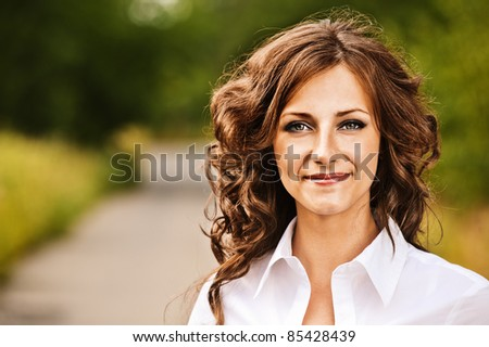 Portrait of beautiful young brunette woman wearing white blouse at summer green park. - stock photo