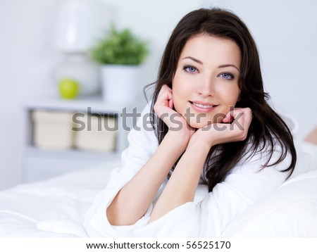 Portrait of beautiful young brunette woman with attractive smile - indoors - stock photo