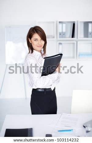 portrait of beautiful young business woman holding folder in bright office at office - stock photo