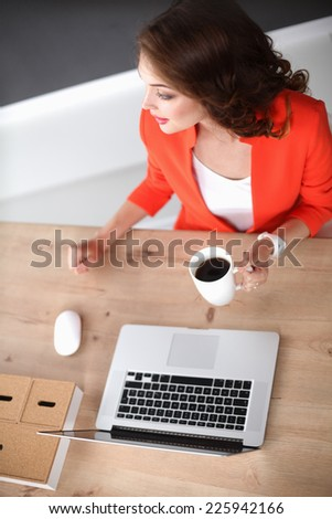 Portrait of beautiful young business woman working on a laptop at office  - stock photo