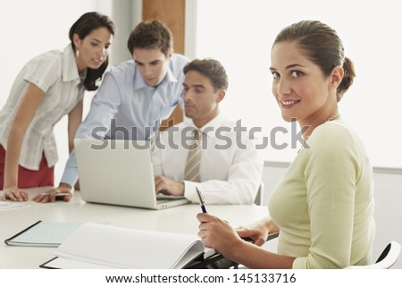 Portrait of beautiful young businesswoman sitting with colleagues working on laptop at desk in office