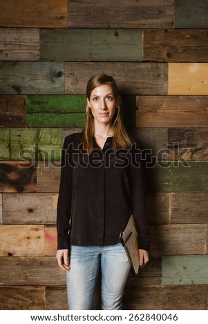 Portrait of beautiful young businesswoman standing against a wooden wall looking at camera. Caucasian woman in casuals in office. - stock photo