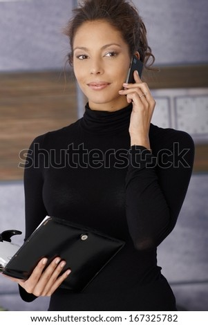 Portrait of beautiful young businesswoman talking on mobile phone, holding personal organizer, smiling.