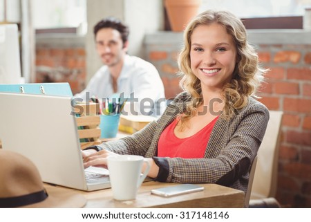 Portrait of beautiful young businesswoman working in creative office