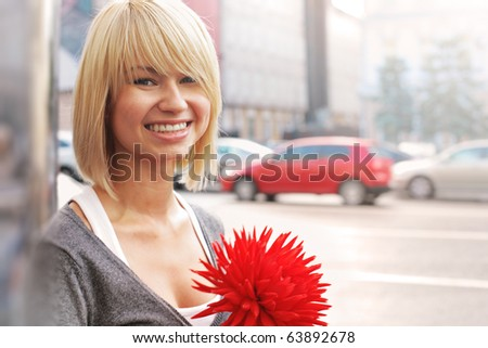 Portrait of beautiful young Caucasian woman with red flower smiling over city street background. Closeup, shallow DOF.