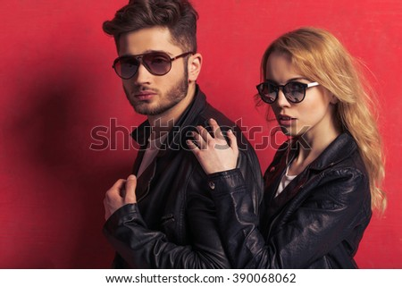Portrait of beautiful young couple in leather jackets and sunglasses looking at camera, standing against red background