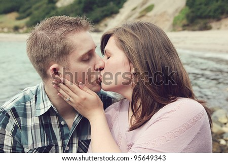 Portrait of beautiful young couple outside kissing in summer