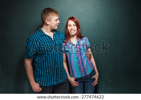 Portrait Of Beautiful Young Couple Over Dark Green Wall. Boy embraces his girlfriend gently and they happily smiling. Red-haired woman and blonde man in check shirts. Love story.  - stock photo