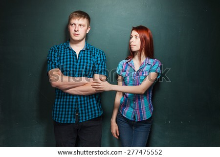 Portrait Of Beautiful Young Couple Over Dark Green Wall. Hard times in relationships. Woman apologizes. Reconciliation. Red-haired woman and blonde man in check shirts. - stock photo