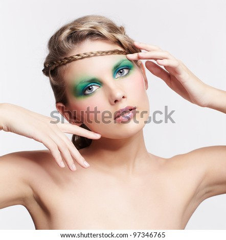 portrait of beautiful young dark blonde woman with creative braid hairdo and green eye shades make up on gray