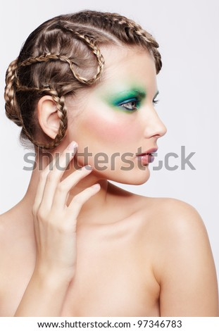 portrait of beautiful young dark blonde woman with creative plait hairdo and green eye shades touching her cheek