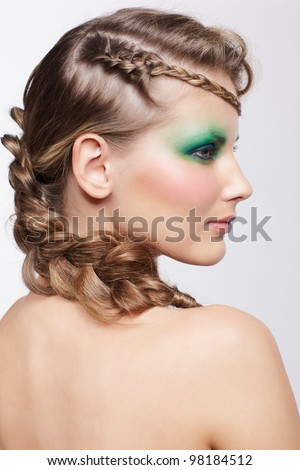 portrait of beautiful young dark blonde woman with creative plait hairstyle and green eye shades make up posing on gray