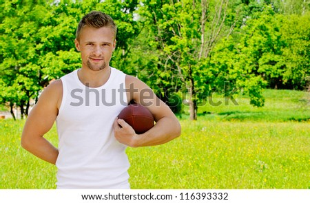 Portrait of beautiful young dressed in white sportsman with rugby ball, against green of summer park.