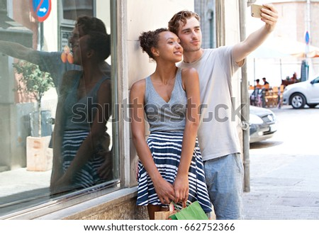 Portrait of beautiful young ethnically diverse tourist couple visiting city, joyfully smiling carrying shopping bags, taking selfies pictures with smart phone. Travel technology recreation lifestyle.