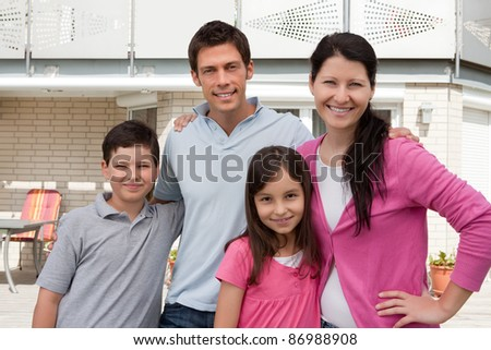 Portrait of beautiful young family standing together outside their new house
