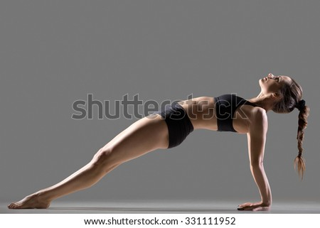Portrait of beautiful young fit woman in sportswear shorts doing sport exercise, Purvottanasana, Upward Plank posture, shoulders, chest, ankles, arms, wrists, abs, studio image, gray background - stock photo