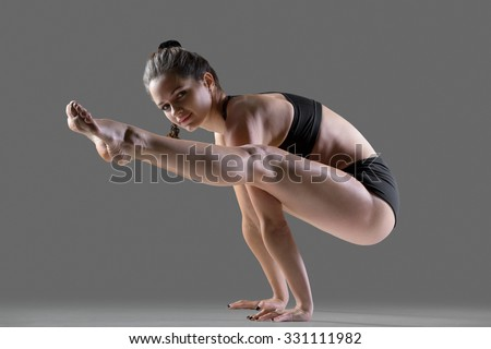 Portrait of beautiful young fit woman in sportswear shorts doing sport exercises, handstand Tittibhasana, Firefly posture, full length, side view, studio image on gray background - stock photo