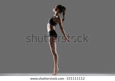 Portrait of beautiful young flexible fit woman in sportswear doing sport exercises for spine and shoulders, standing on tip toes, bending backwards, full length, side view, studio, gray background - stock photo